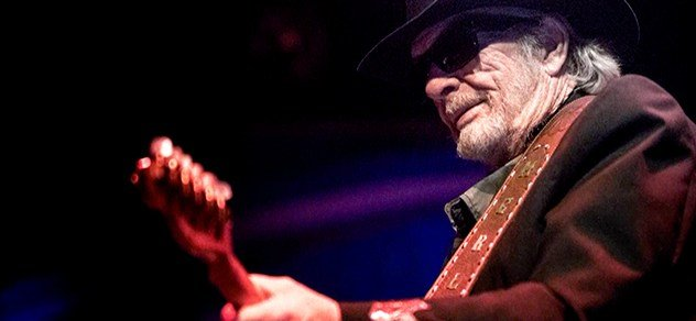 Merle Haggard plays on stage.