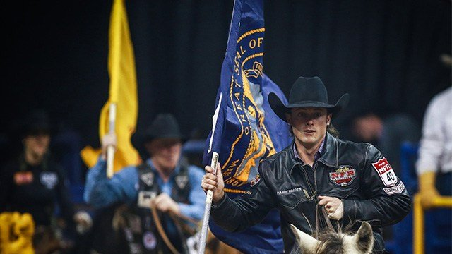 Hardy Braden bears the flag of his state during the seventh performance of the Wrangler National Finals Rodeo.