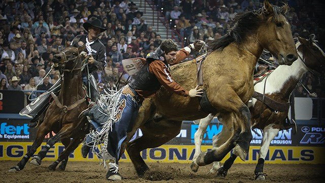 Tanner Aus found himself hung up during the eighth performance of the Wrangler National Finals Rodeo in Las Vegas, NV.