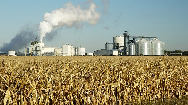 A fuel refinery and a corn field.