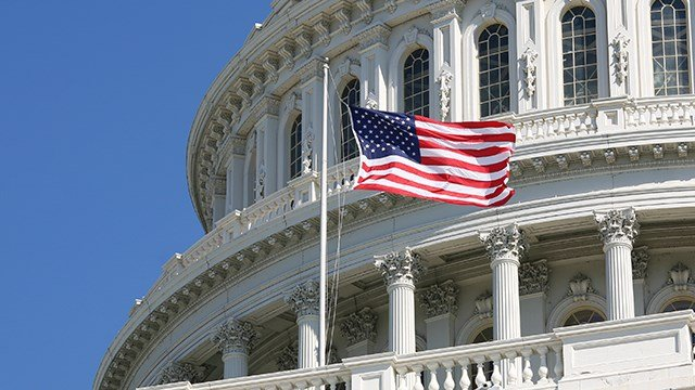 The U.S. flag flies in front the dome of the U.S. Capitol Building.