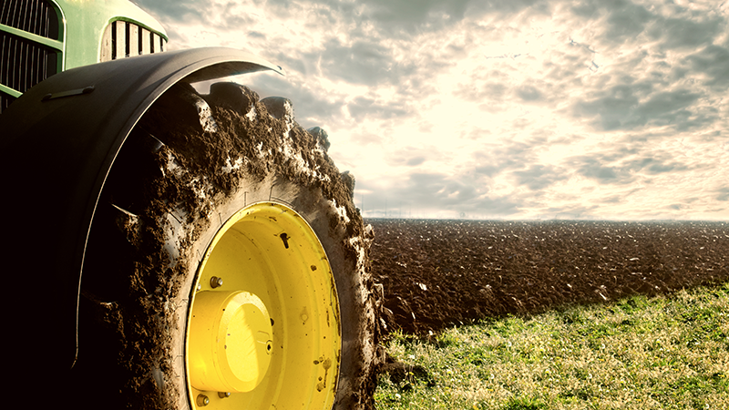 A dirt-caked tractor tire in a freshly plowed field.